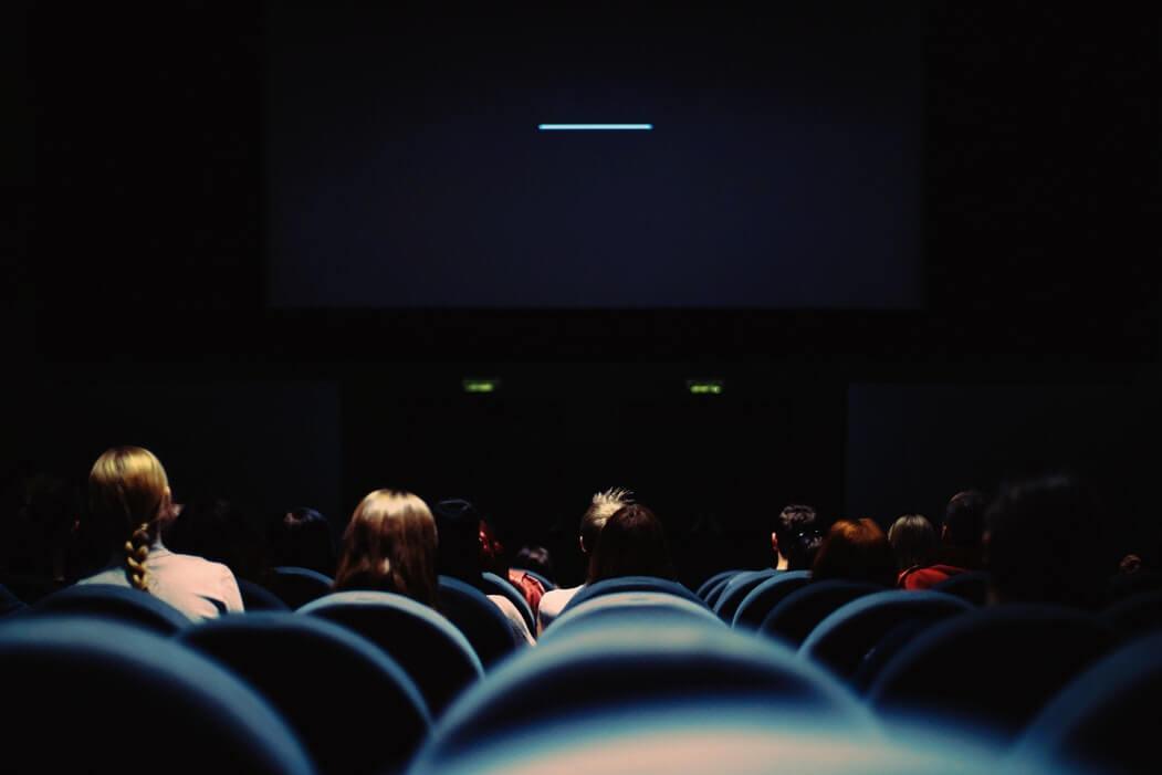 Sala de cinema com pessoas esperando pelo filme.