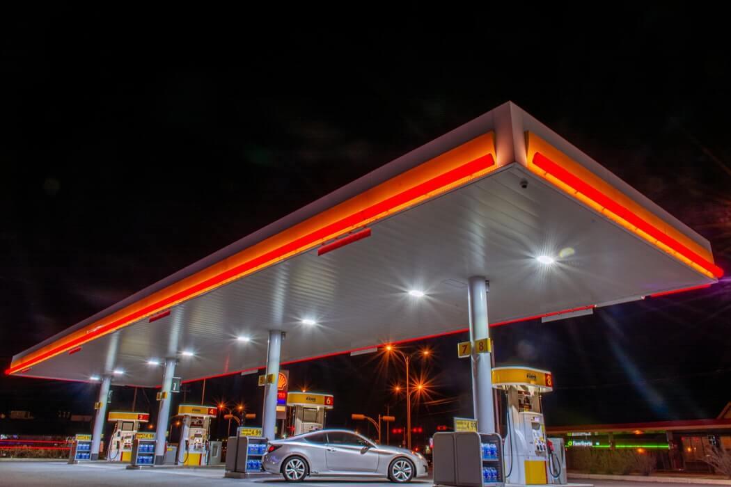 Posto de gasolina com luzes de LED laranja na fachada.