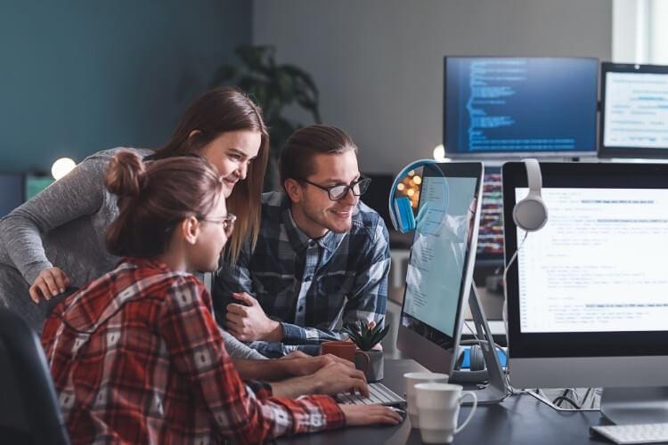 Equipe ao redor do computador, trabalhando junto e sorrindo.