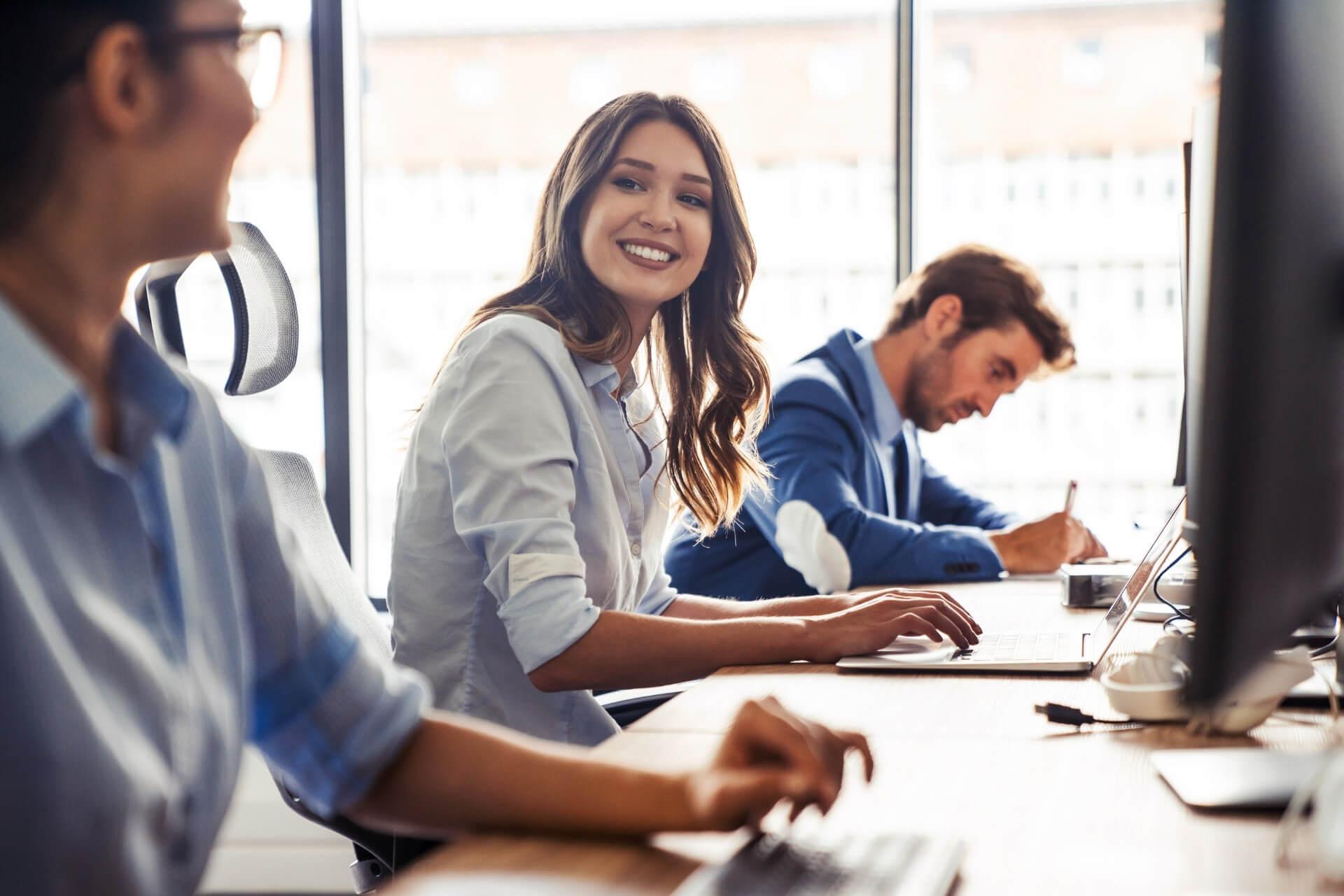 Equipe De Trabalho Sorrindo Entre Si, Em Frente Ao Computador.