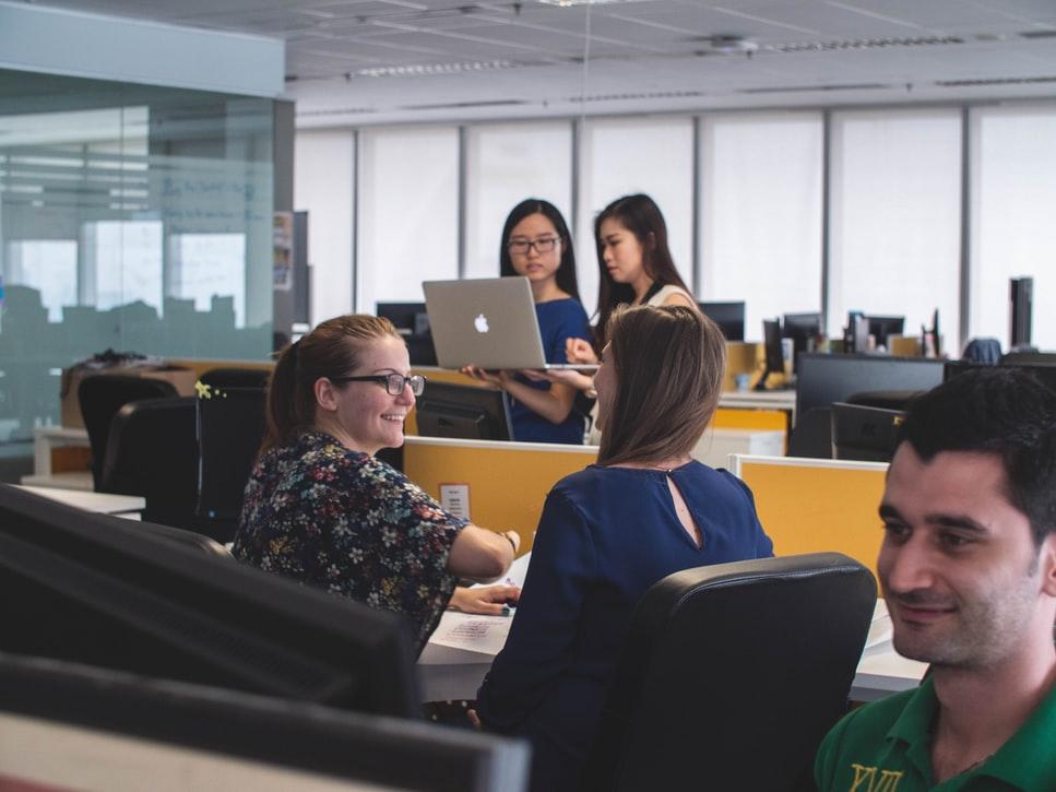 Profissionais no local de trabalho agradável, sorrindo e conversando uns com os outros.