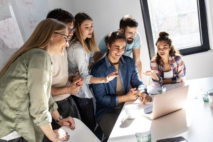 Equipe de trabalho formada de homens e mulheres reunida ao redor do computador.