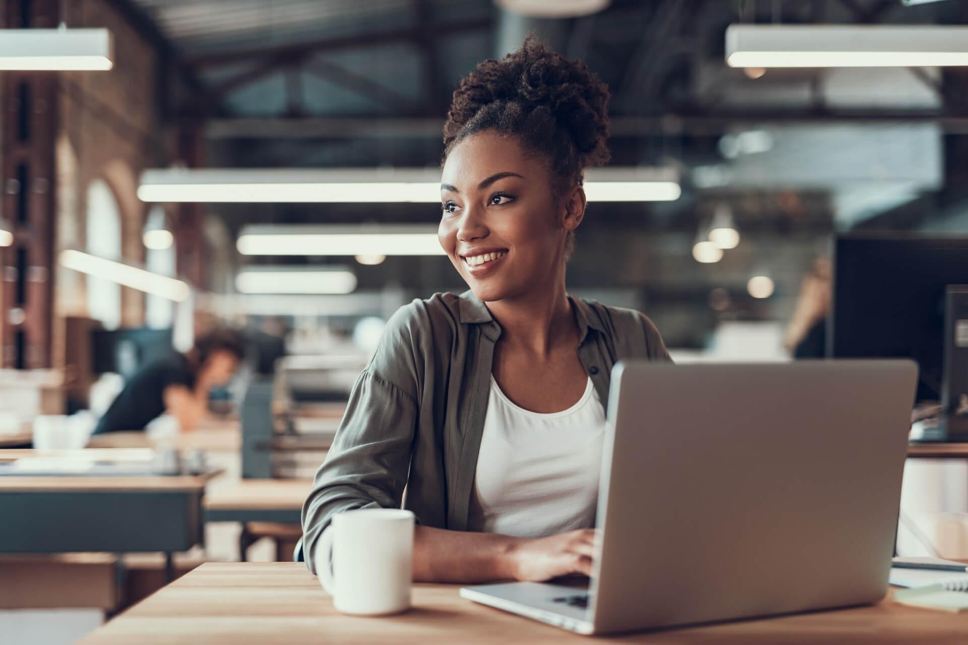 Mulher Negra Mexendo Ao Computador, Olhando Para O Lado E Sorrindo.