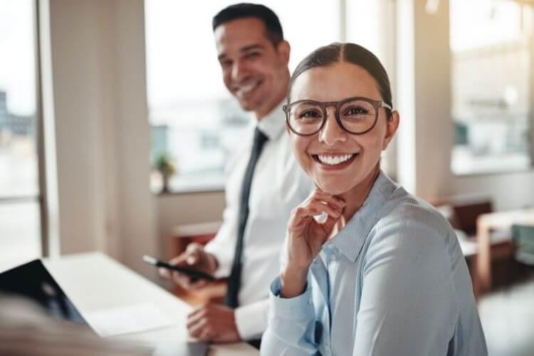 Mulher e homem olhando para a câmera e sorrindo, com roupas sociais.