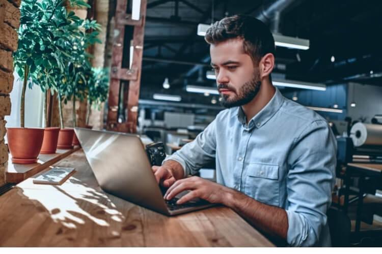 Homem de camisa digitando em um notebook.