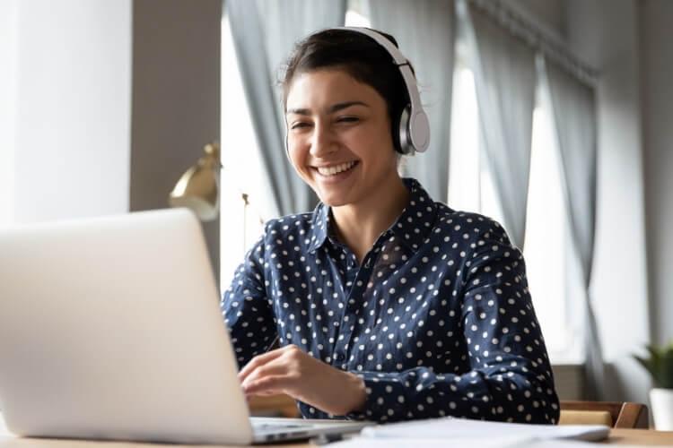Mulher de fone de ouvido sorrindo enquanto olha para o notebook.
