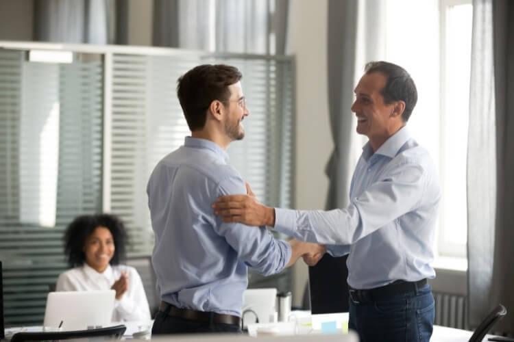 Homens de roupa social apertando as mãos um do outro.
