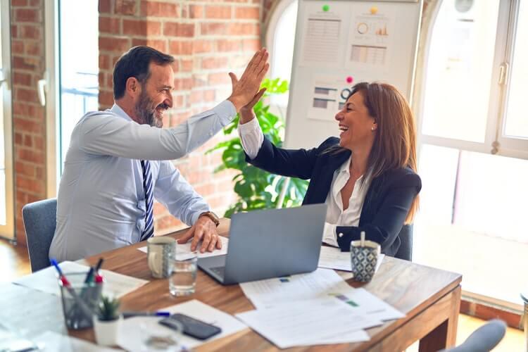 Homem e mulher de negócios batendo as mãos em comemoração.