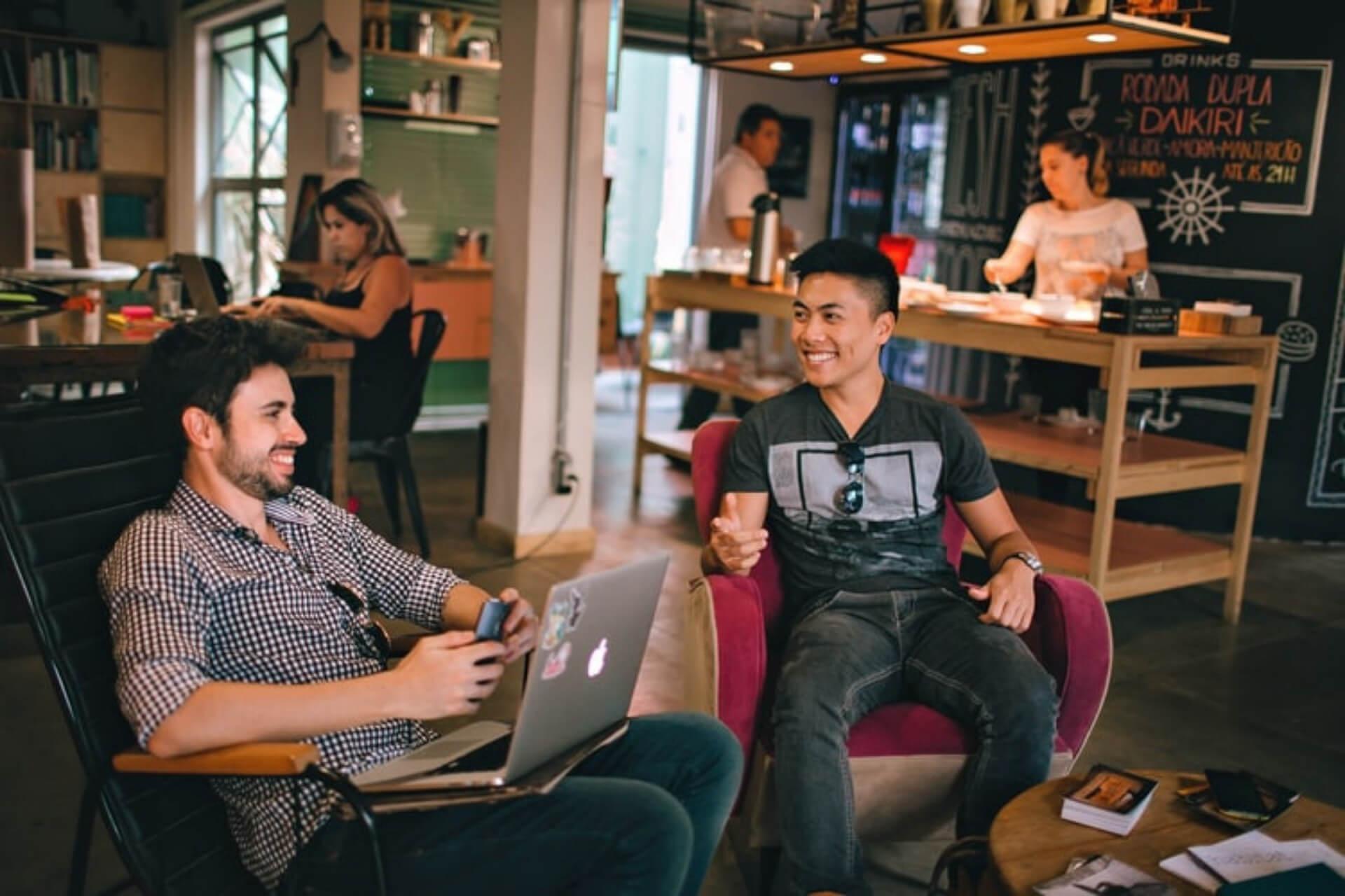 Dois Homens Sentados Na Empresa, Sorrindo Um Para O Outro.