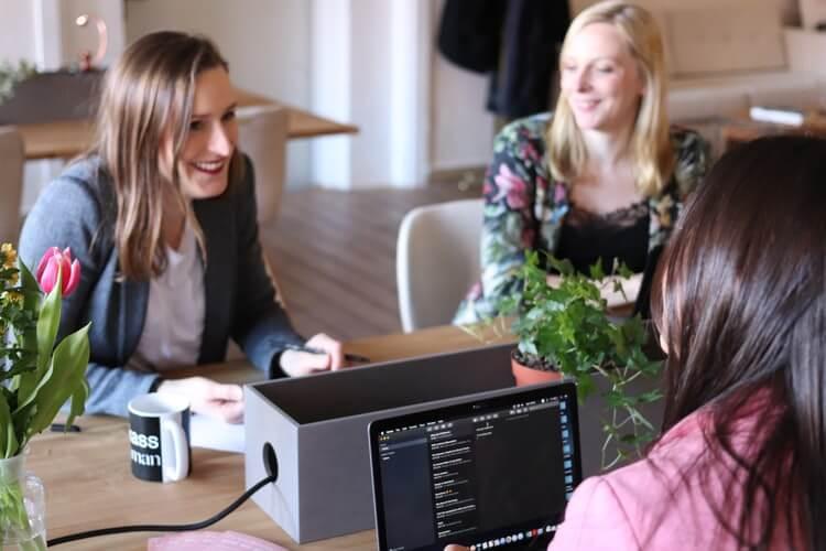 Mulheres sentadas à mesa de trabalho, mexendo no computador e rindo.