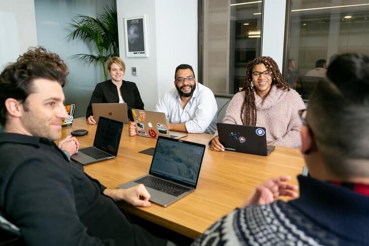 Equipe de trabalho repleta de variedade ao redor de uma mesa, sorrindo.