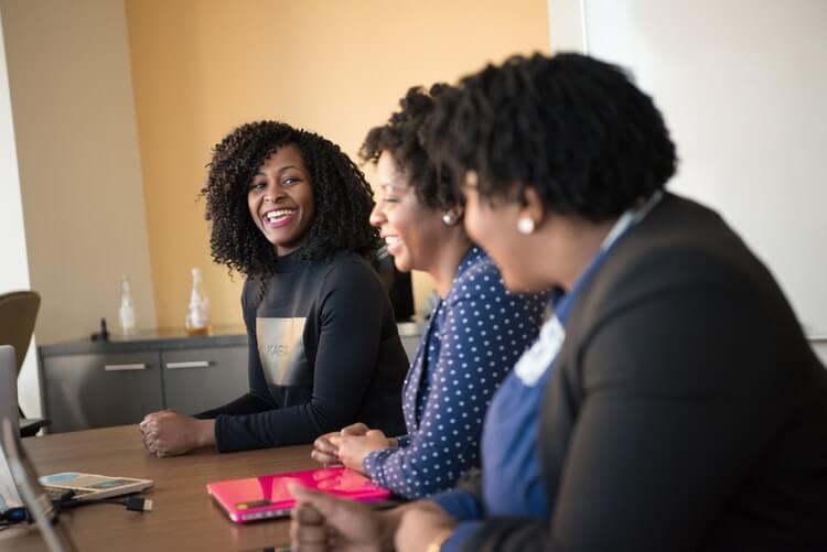 Mulheres negras sentadas à mesa, conversando e trabalhando.