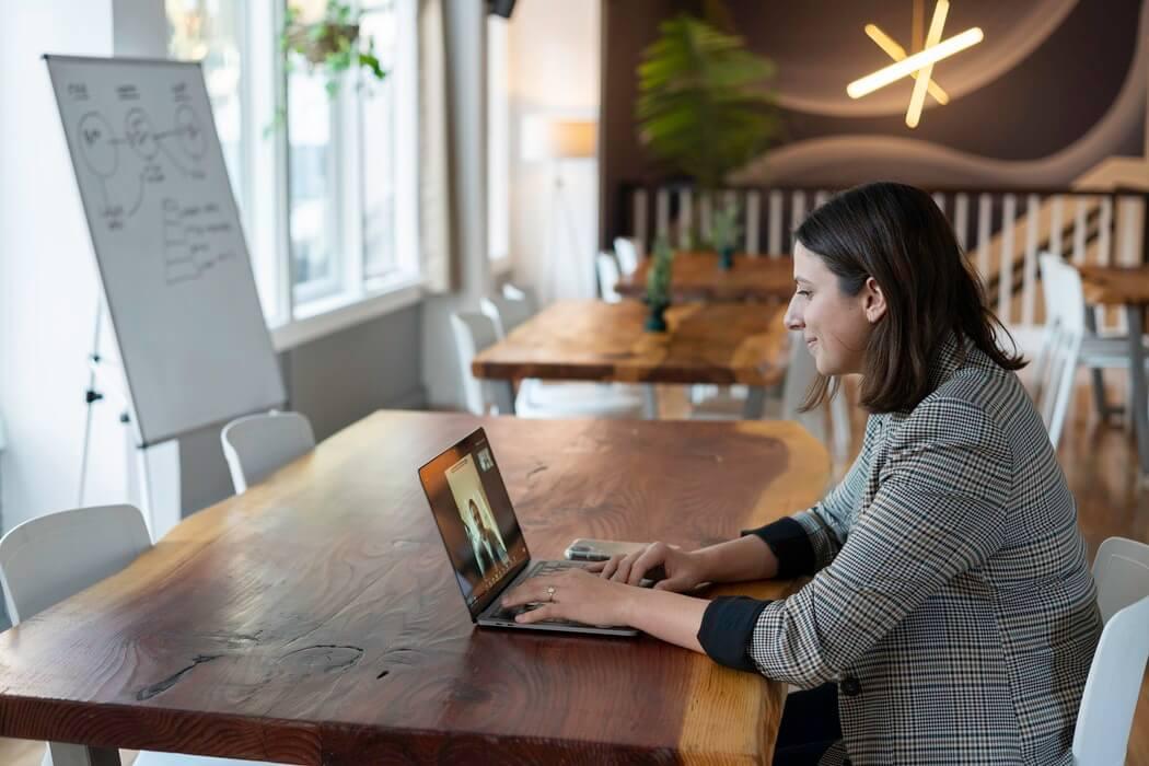 Mulher em uma mesa de madeira, assistindo curso online de liderança.