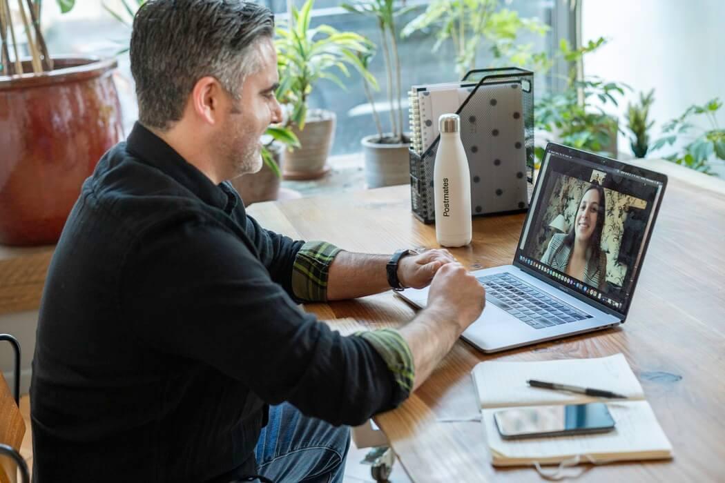 Homem assistindo curso de liderança online e gratuito ministrado por mulher.